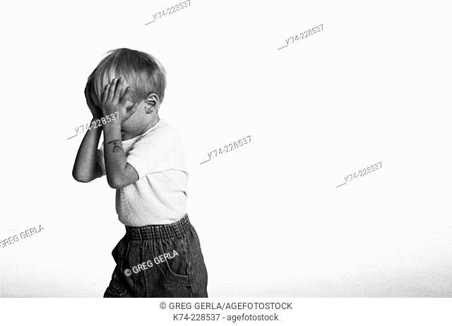 image of young boy with hands over face
