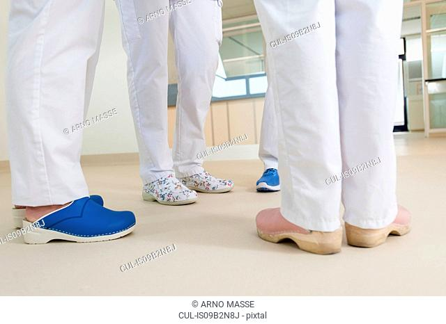Low section of group of nurses wearing surgical scrubs and clogs