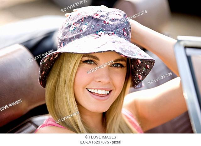 A young woman sitting in a black sports car wearing a summer hat, close up