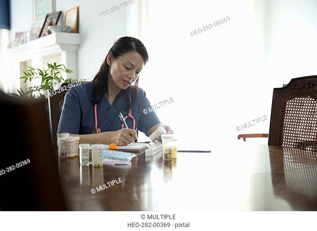 Home caregiver writing notes on prescription medication at dining table