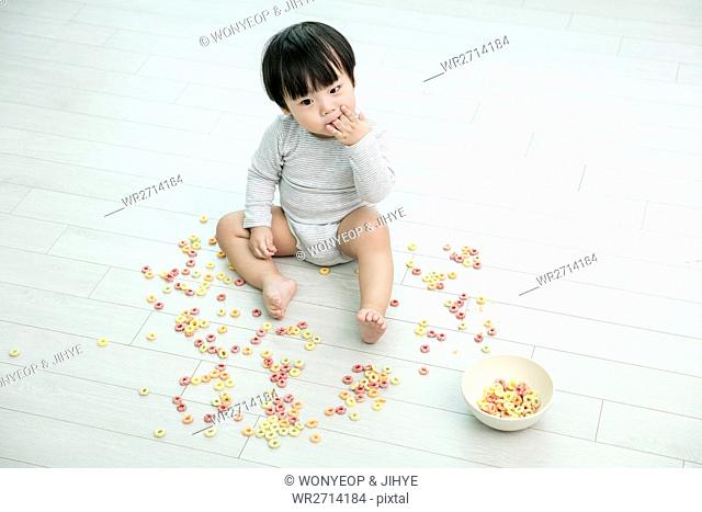 Baby boy making mess with cereal
