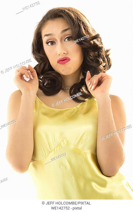 Beautiful young woman half length in vintage yellow dress, with a sassy look