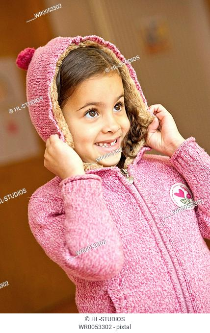 Young girl putting on a hood
