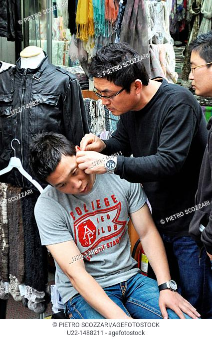 Seoul (South Korea): sellers cleaning ears each other at the Namdaemun Market