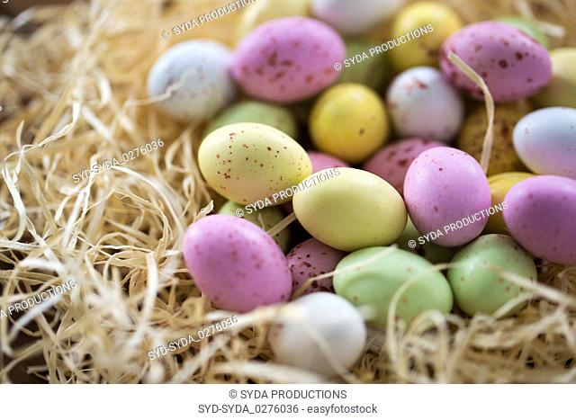 close up of easter egg candies in straw nest