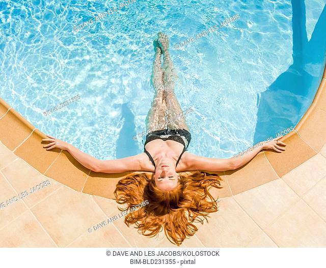 Woman wearing bikini laying at edge of swimming pool