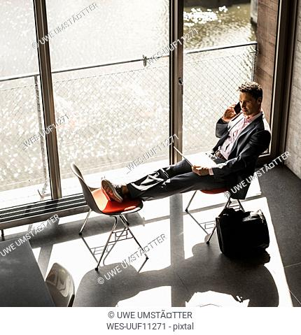 Businessman sitting at the window with feet up, working on laptop and making a call
