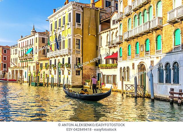 A gondolier in his gondola in the Grand Canal of Venice in front of old palaces