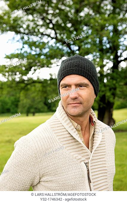 Portrait of man with a beanie standing in a park