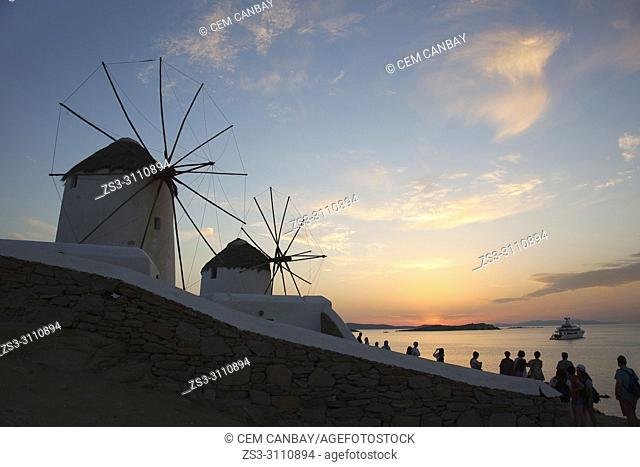 Tourists near the traditional windmills by the sea in Mykonos town at sunset, Mykonos, Cyclades Islands, Greek Islands, Greece, Europe