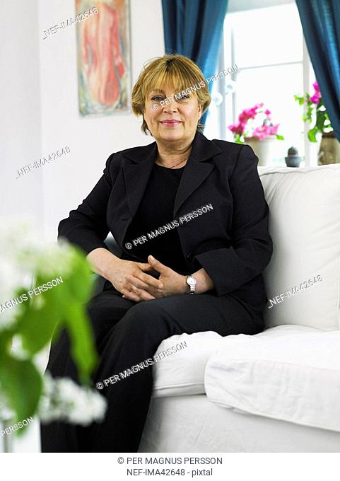 A smiling woman sitting on her couch