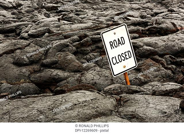 Road sign covered with Pahoehoe lava; Island of Hawaii, Hawaii, United States of America
