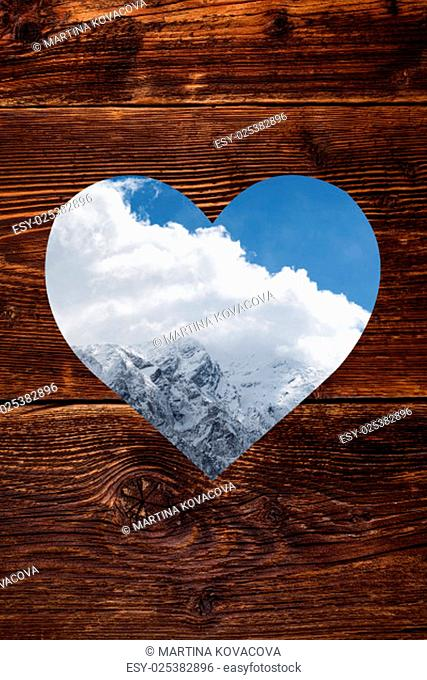 Austrian Alps in heart shape window on vintage wooden background. Snow covered mountain. Winter