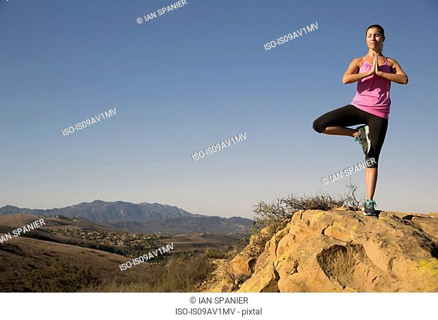 Mature woman practicing yoga tree pose on hill, Thousand Oaks, California, USA