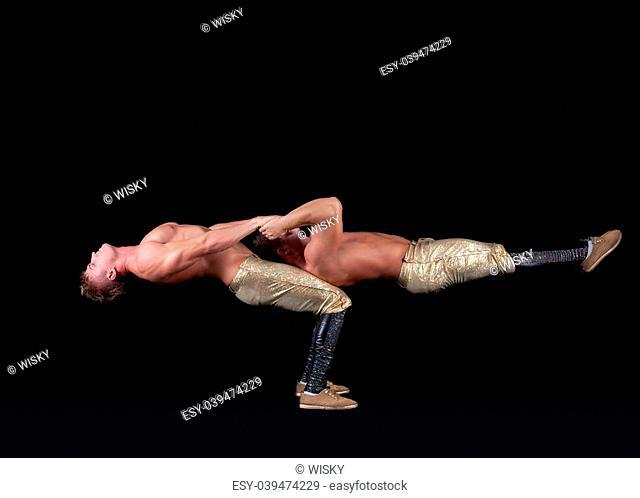 Two seminude acrobats posing keeping balance, on black background