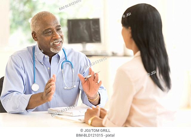 Black doctor and patient talking in office