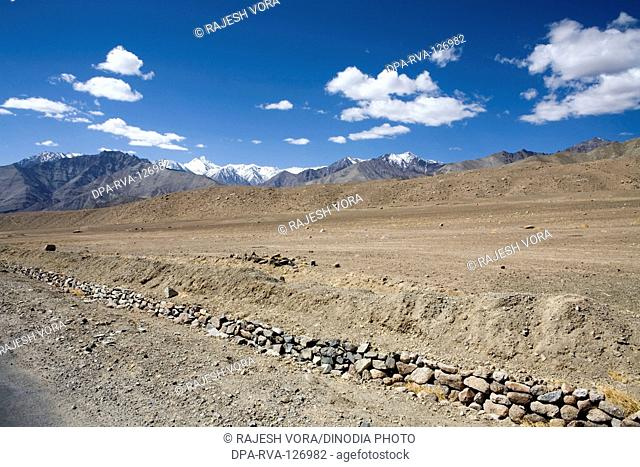 Typical landscape of Ladakh with sandy rocky and snow covered mountains on Leh Kargil road ; Ladakh ; Jammu and Kashmir ; India
