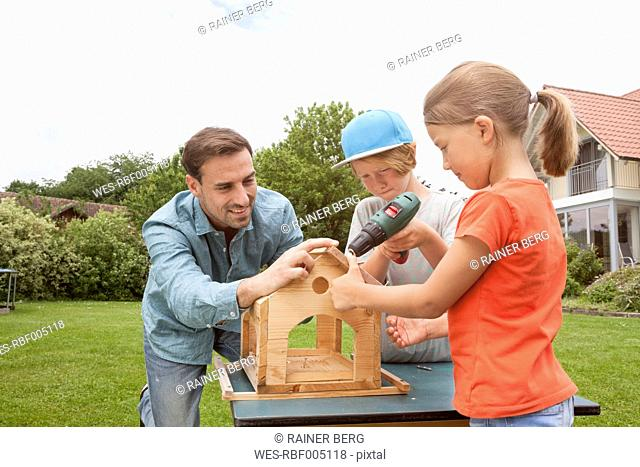 Father and children building up a birdhouse together