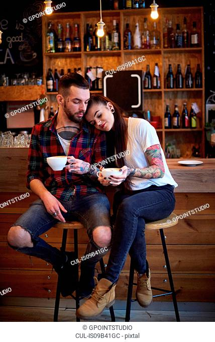 Couple sitting side by side on stools in cafe, head on shoulder