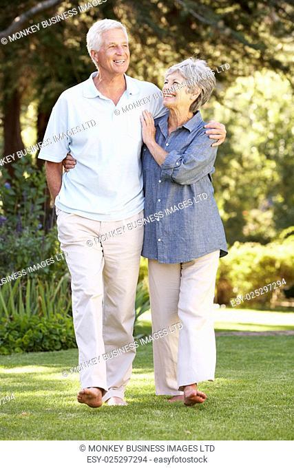 Senior Couple Walking In Garden At Home