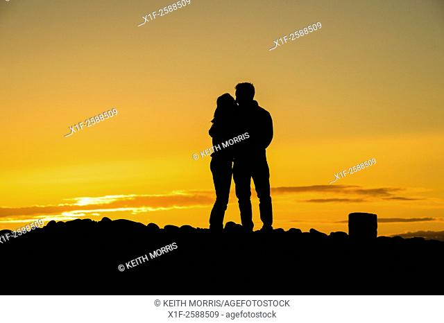 Romance: A young couple embracing in sillhouette at sunset