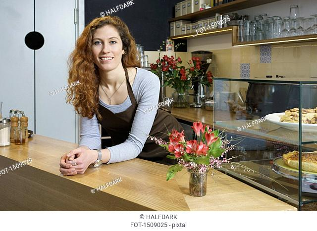 Portrait of smiling young woman standing by table at cafe