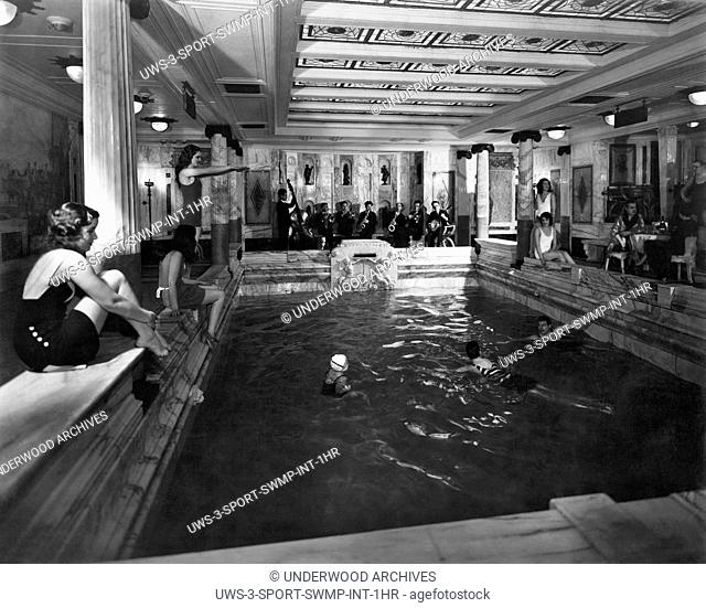 Italy: c. 1927.First class passengers lounging around their indoor pool with a jazz band on the Italian passenger liner MS Vulcania
