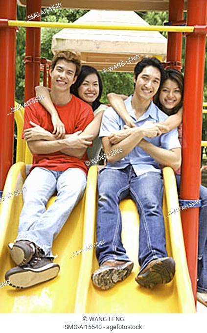 Young adults in playground, smiling at camera, portrait