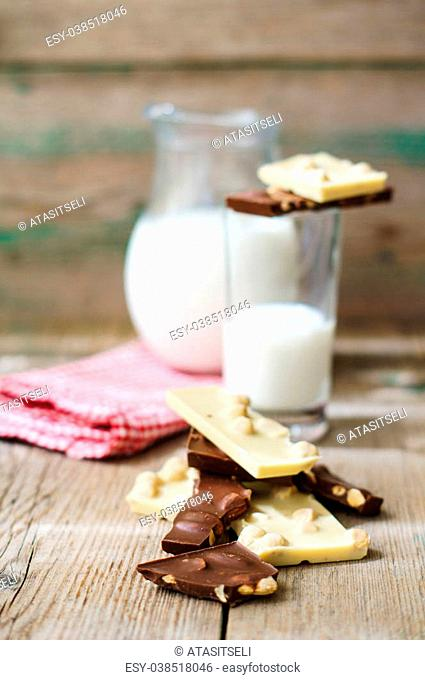 Glass of milk and bars of two types of chocolate