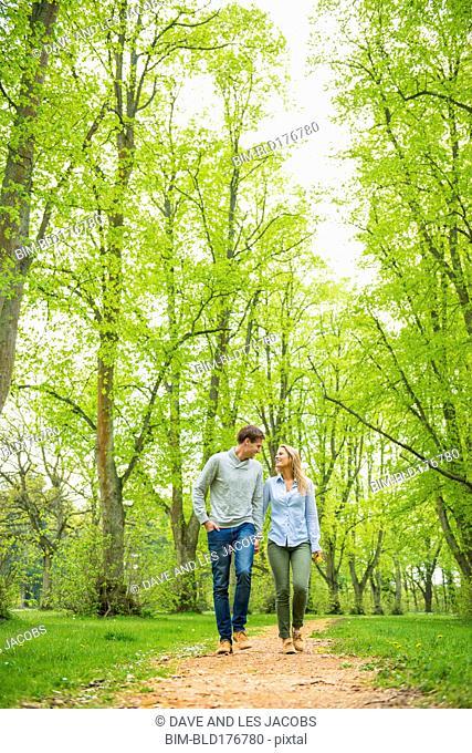 Caucasian couple walking on dirt path
