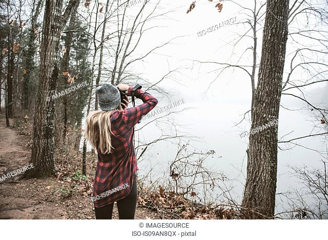 Young woman photographing misty lake