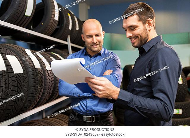 customer and salesman at car service or auto store