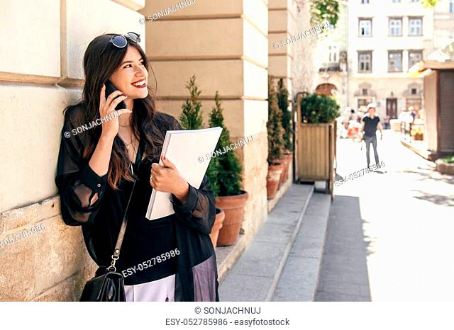 beautiful stylish woman walking in sunny city street, holding phone and magazine. happy hipster girl dressed in fashionable outfit