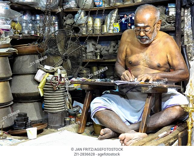 man in small shop in thiruvannamalai, india