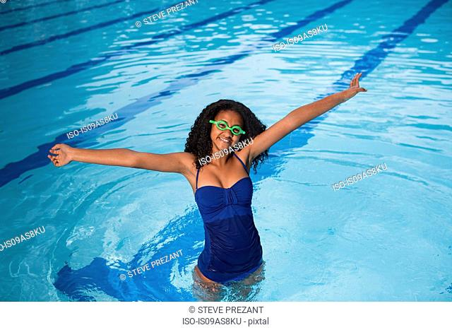 Portrait of girl standing in swimming pool wearing swimming goggles, arms raised, looking at camera smiling