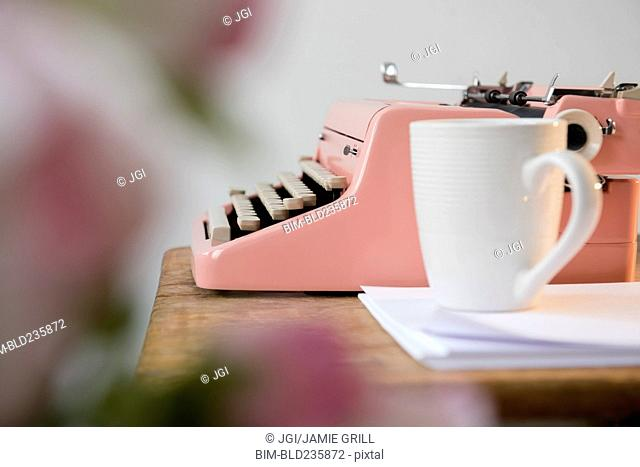 Coffee cup on pile of paper near pink typewriter