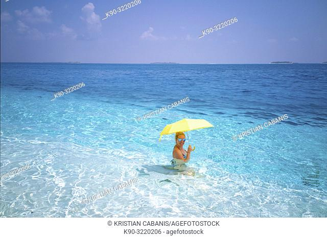 Young caucasian woman sitting in the turquoise water close to the beach, Dharavandhoo, Baa Atoll, Maldives, Indian Ocean, South Asia