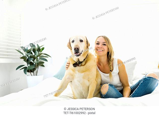 Portrait of blond woman with golden retriever