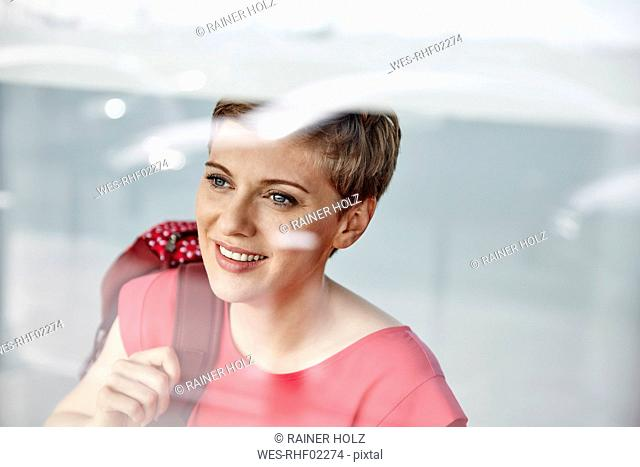 Portrait of smiling woman with backpack behind windowpane