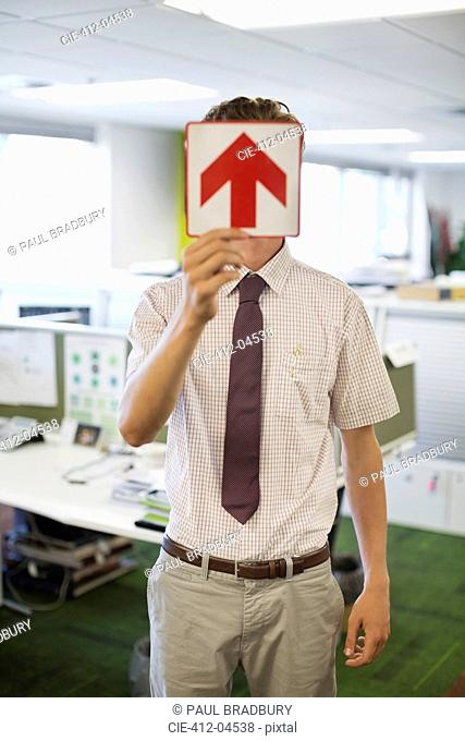 Businessman holding arrow sign in office