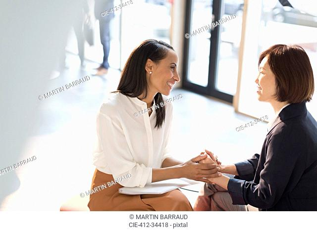 Smiling businesswomen holding hands in sunny office lobby