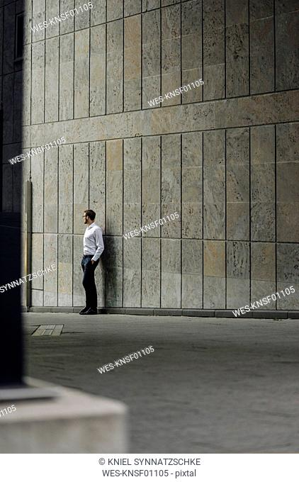 Businessman standing at a wall