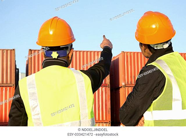 Two workers inspection on stack of containers