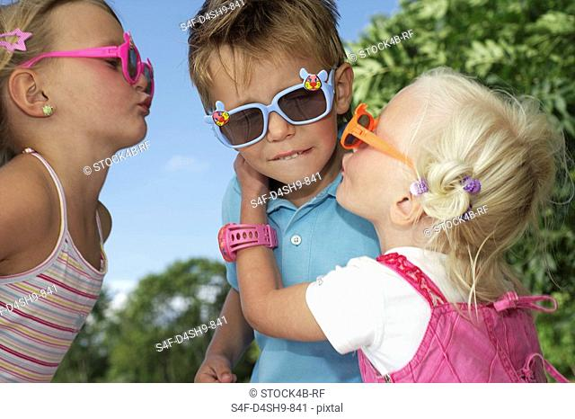 Two girls trying to kiss a boy, all wearing sunglasses, close-up