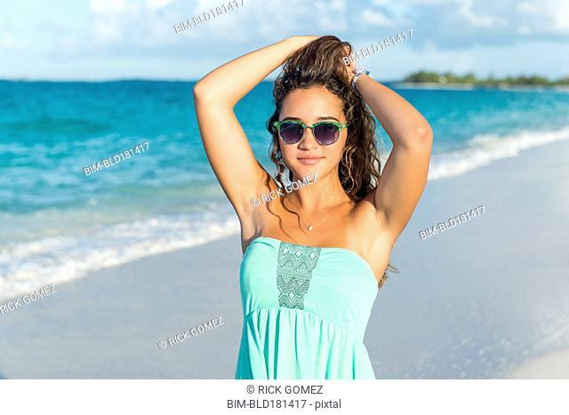 Hispanic teenage girl standing on beach