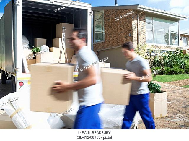 Movers carrying cardboard boxes in driveway past moving van
