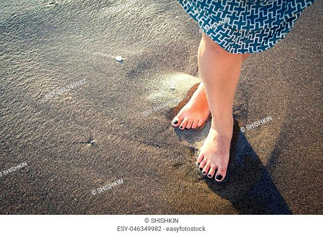 Beautiful bare feet on the beach. Sea foam washes female legs. Image of feet in the sand on the shore in the wave. Sunshine on the ocean in the wave