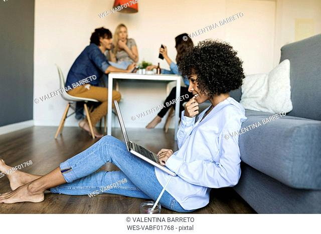 Woman sitting on floor using laptop with friends in background