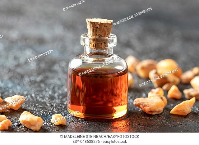 A bottle of styrax benzoin essential oil and resin on a dark background