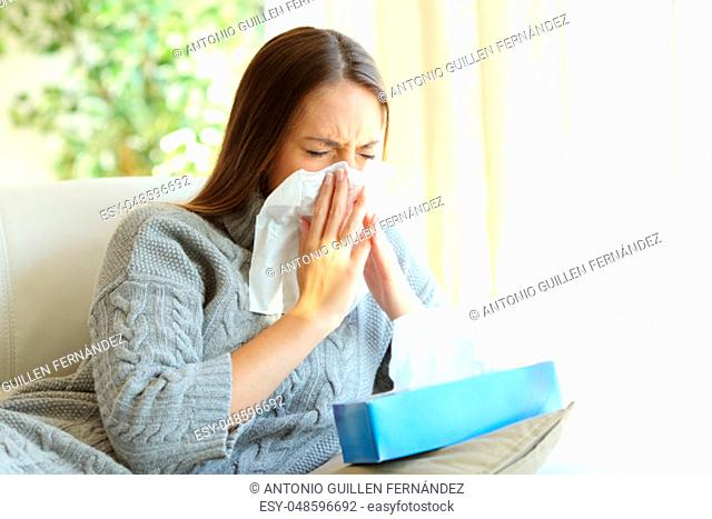 Woman blowing in a wipe suffering flu symptoms sitting on a sofa at home in winter